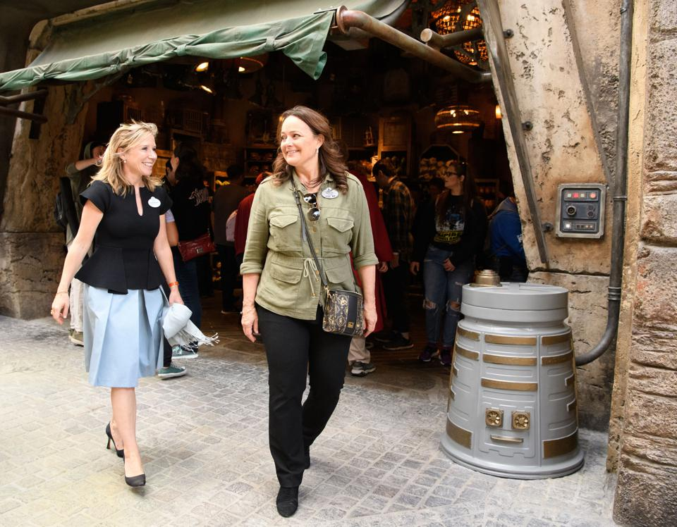 Catherine Powell (left), President of Disney Parks Western Region, walks the streets of Batuu with Kris Theiler