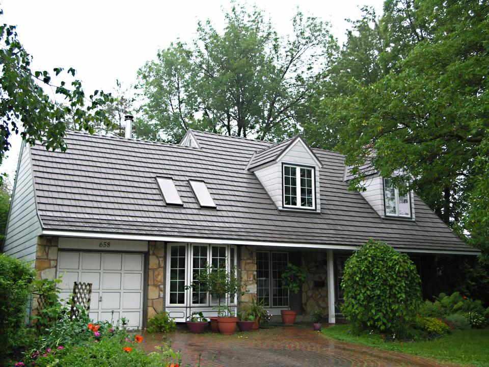 This metal shingle roof is the color of a wood shake roof that has been weathered. The roof is by Isaiah Industries.