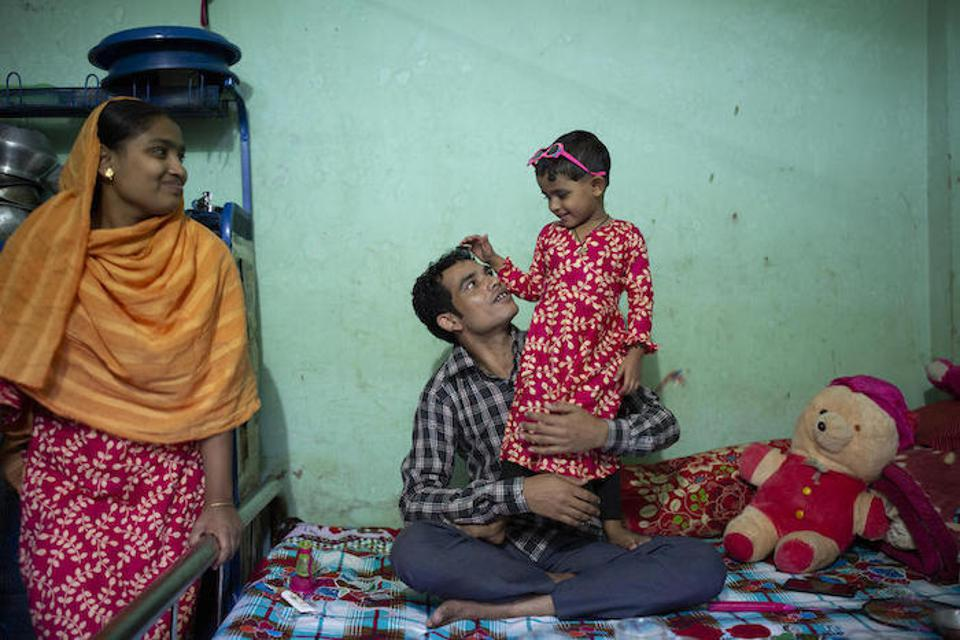 Shumi Akhter, 20, looks on as her husband, Jamal Hossain, 26, plays with their 2 1/2-year-old daughter, Jui, at their home near the Northern Tosrifa Group garment factory where they work in Gazipur, outside Dhaka, Bangladesh.