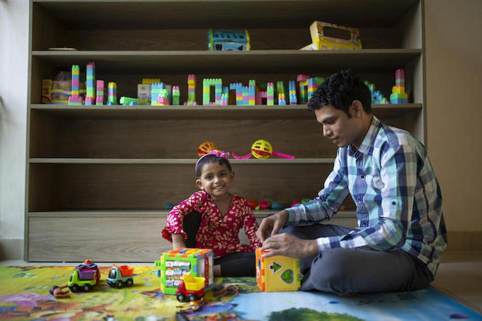 Jui, 2 1/2, and her father, Jamal Hossain, play at UNICEF-backed Early Childhood Development center at the Northern Tosrifa Group garment factory in Gazipur, outside Dhaka, Bangladesh.