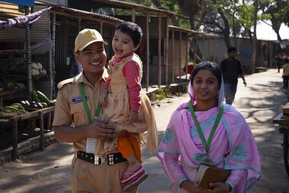 Dressed in his firefighter uniform, Mohammad Jahirul Islam, 28, carries his daughter, Jisha, 3, to the day care center she attends at the garment factory where he and his wife (right) work in Narayangonj, outside Dhaka, Bangladesh.