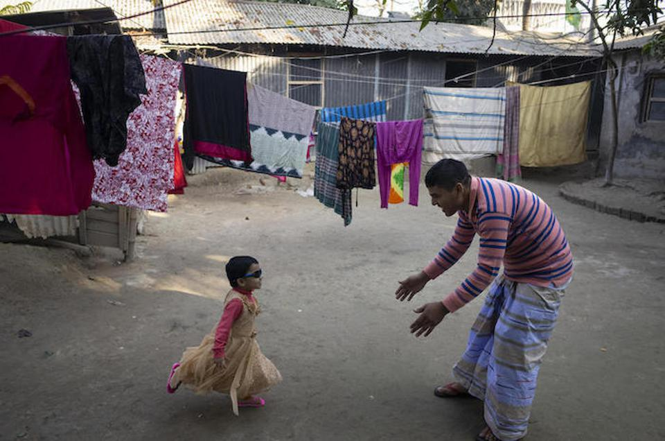 After he comes home from work, Mohammad Jahirul Islam, 28, plays with his daughter, Jisha, 3, in the courtyard outside their home in Narayangonj, outside Dhaka, Bangladesh.