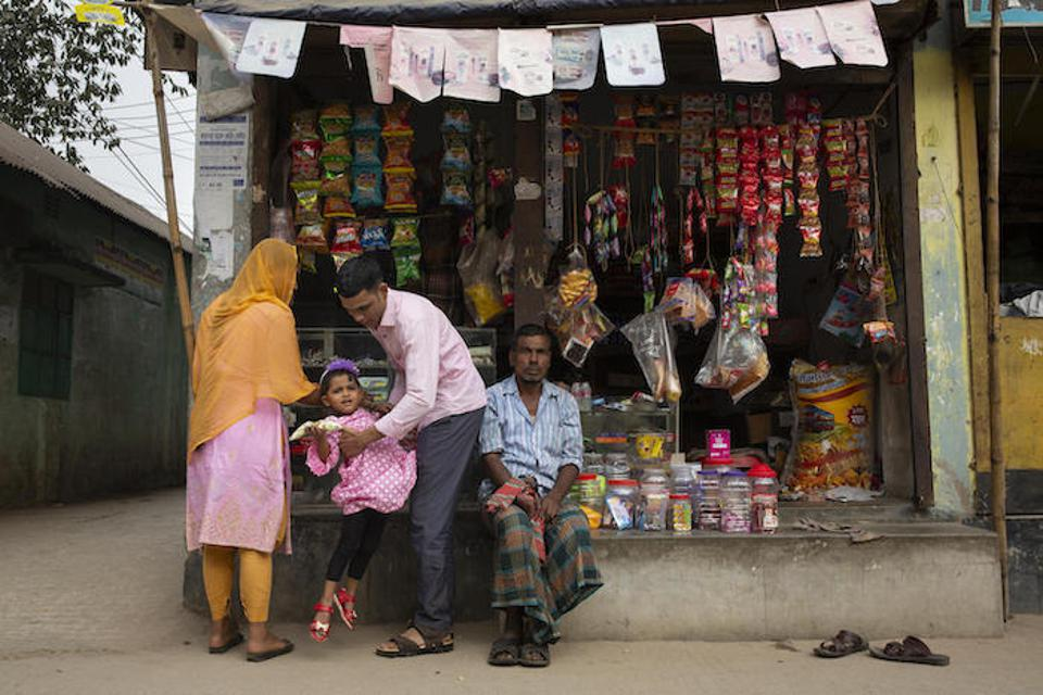 Jamal Hossain, 26, his wife, Shumi Akhter, 20, and their 2 1/2-year-old daughter, Jui, shop for treats near their home in Gazipur outside Dhaka, Bangladesh on December 6, 2018.