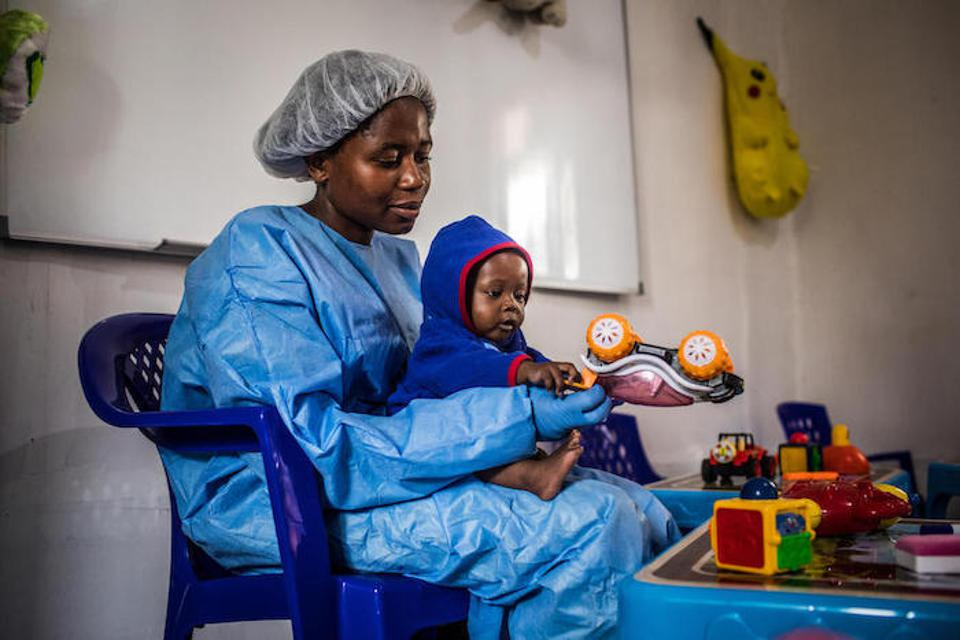 Ruth, a caregiver at the UNICEF-supported nursery in the Ebola Treatment Center of Butembo, plays with Christ-Vie, 7 months, in North Kivu, Democratic Republic of Congo on March 23, 2019.