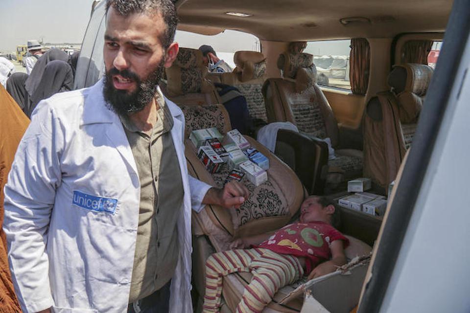 A UNICEF-supported health worker examines a sick child in a mobile health unit in Syria's Al-Hol camp in July 2019.