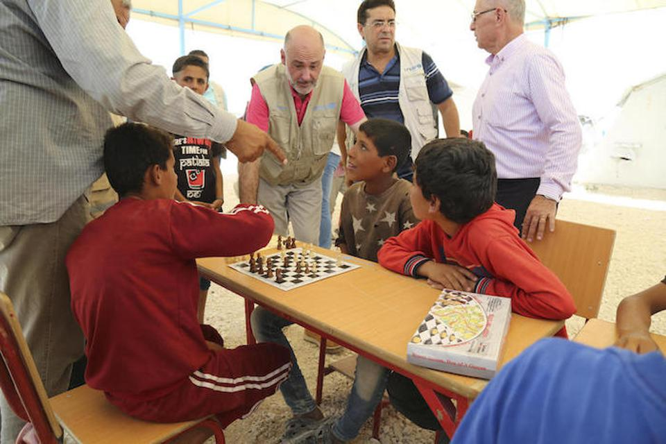 UNICEF Representative in Syria Fran Equiza, center, and colleagues visit with young people playing chess in a UNICEF Child-Friendly Space in Syria's Al-Hol camp in July 2019.