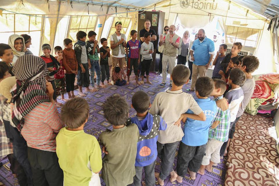 UNICEF Representative in Syria Fran Equiza leads a cooperative game with a group of children in Al-Hol camp near the Syria-Iraq border in July 2019.