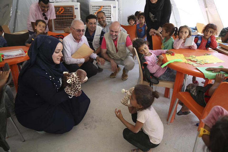A caregiver and a child perform a skit with puppets in a UNICEF Child-Friendly Space at Al-Hol camp in northeastern Syria in July 2019.