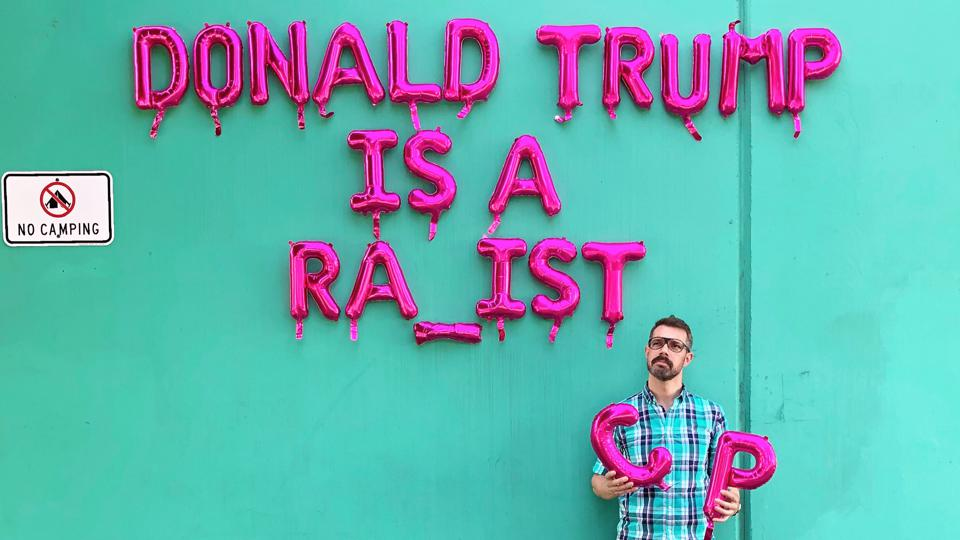 Michael James Schneider stands in front of his balloon art.