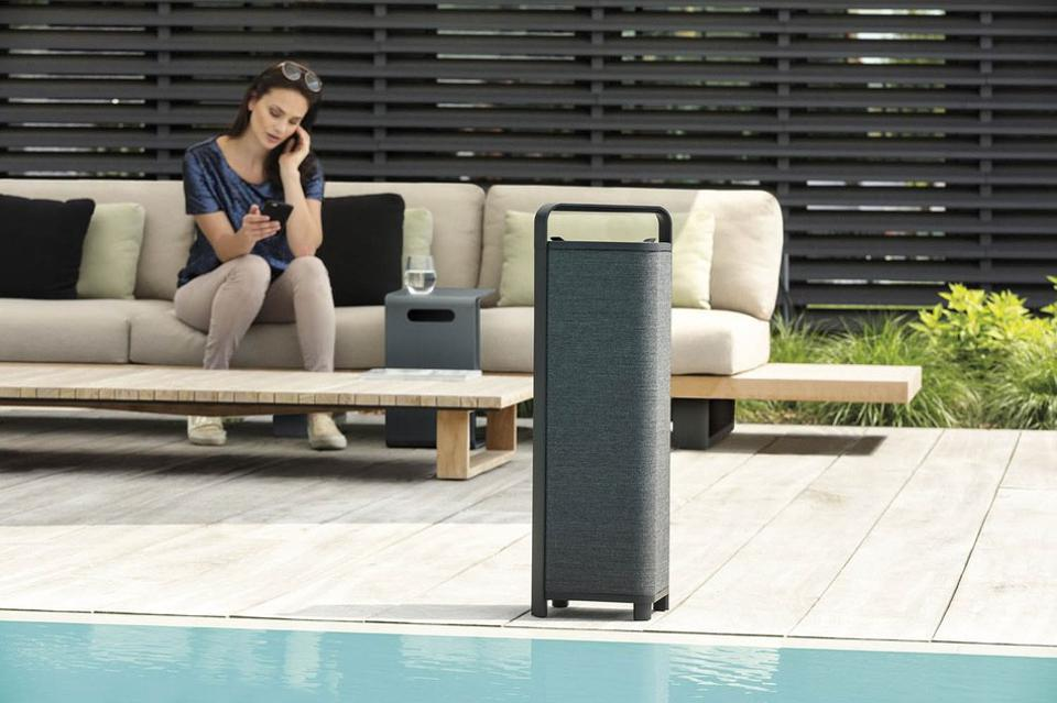 Escape P9 speaker beside pool with woman in background on phone.