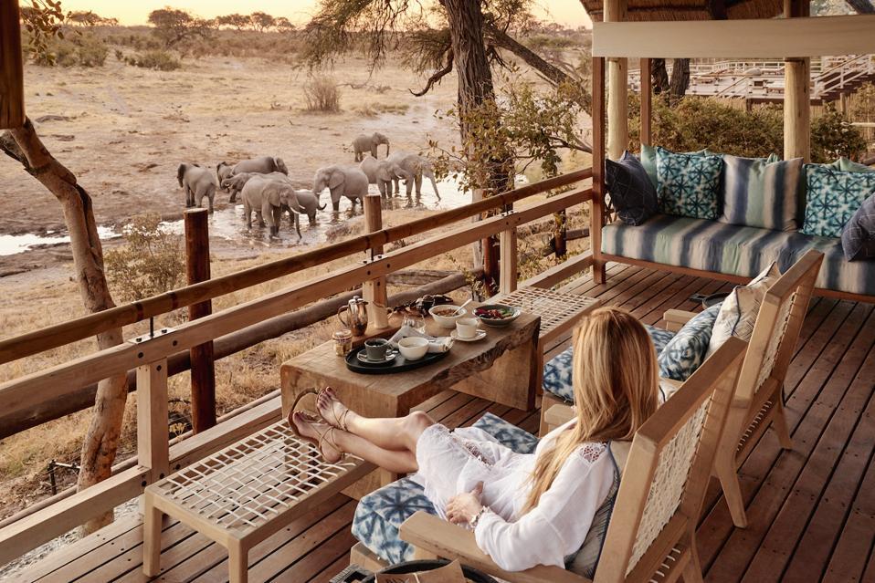 Belmond Savute Elephant Lodge -hotellin vieras nauttii aamiaista omalta terassilta katsellen norsuja kastelukanavassa.