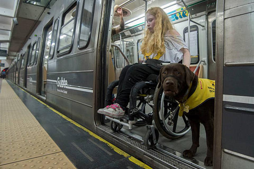 A young woman with blonde hair in a wheelchair exiting the subway with her guide dog.