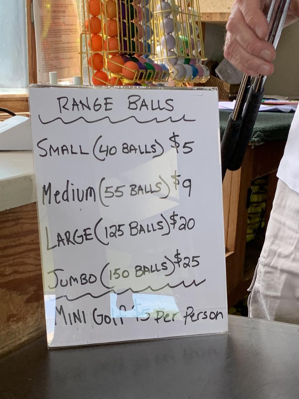 A sign depicts pricing for various-sized buckets of golf balls.