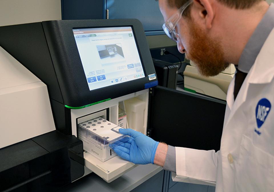 An NSF scientist loads a sample into a genomic DNA sequencing instrument.