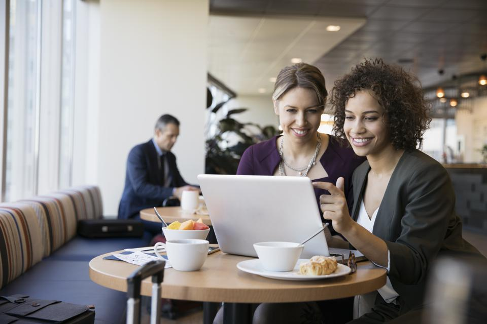 Businesswomen meeting, using laptop at breakfast table in airport lounge