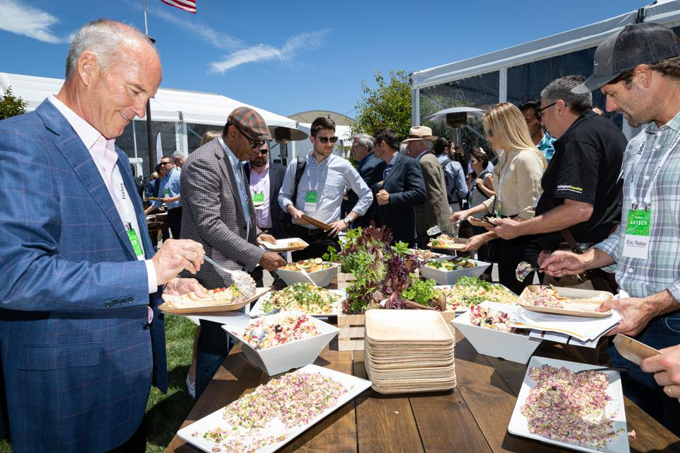 Summit attendees serve themselves at an outdoor table.