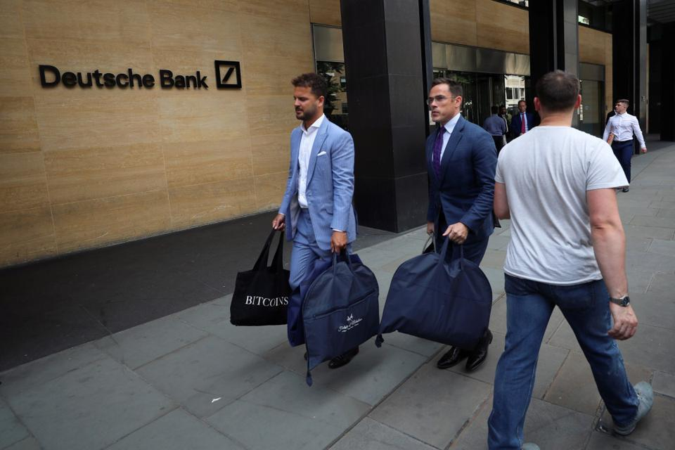 tailors Alex Riley, left, and Ian Fielding-Calcutt carry suit bags outside the Deutsche Bank building in the City of London. Photo: Reuters