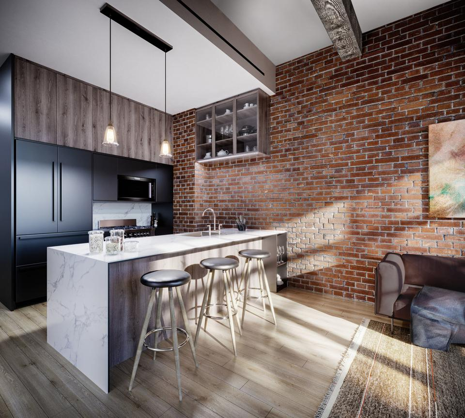 A kitchen island in front of exposed brick.