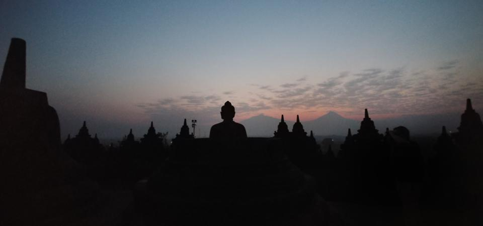 Buddha with Mountains in the Background during Sunrise at Borobudur