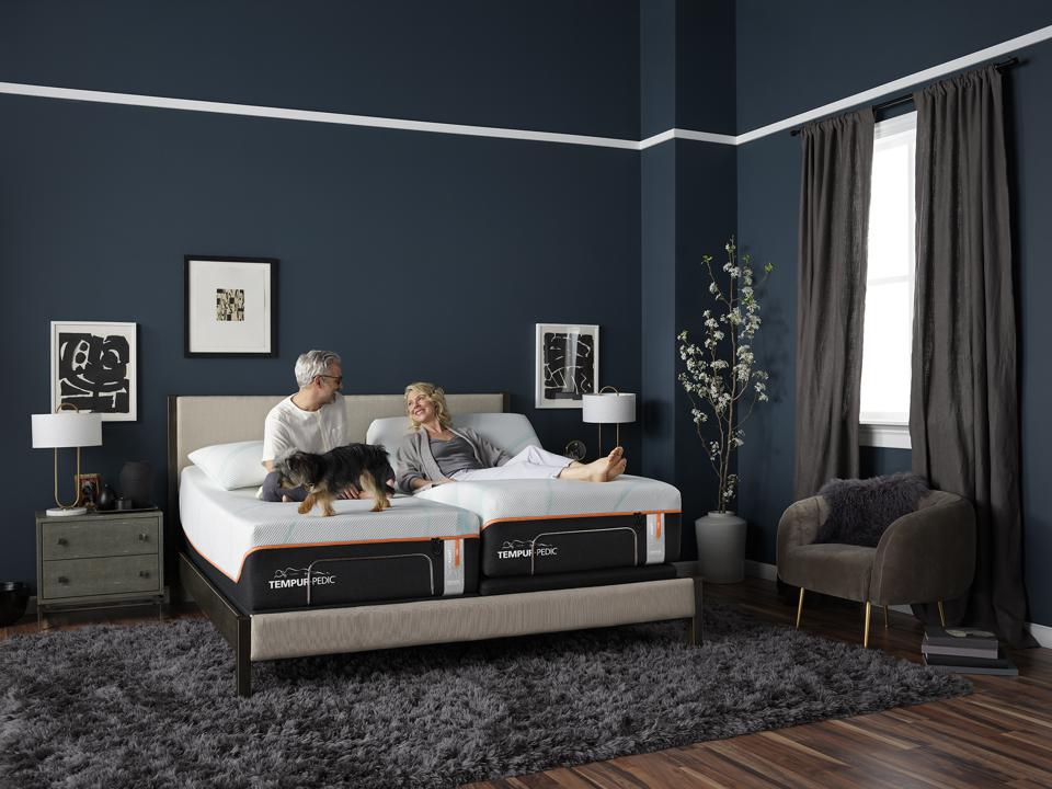 A photograph of a couple on a Tempur-Pedic bed with adjustable bases.