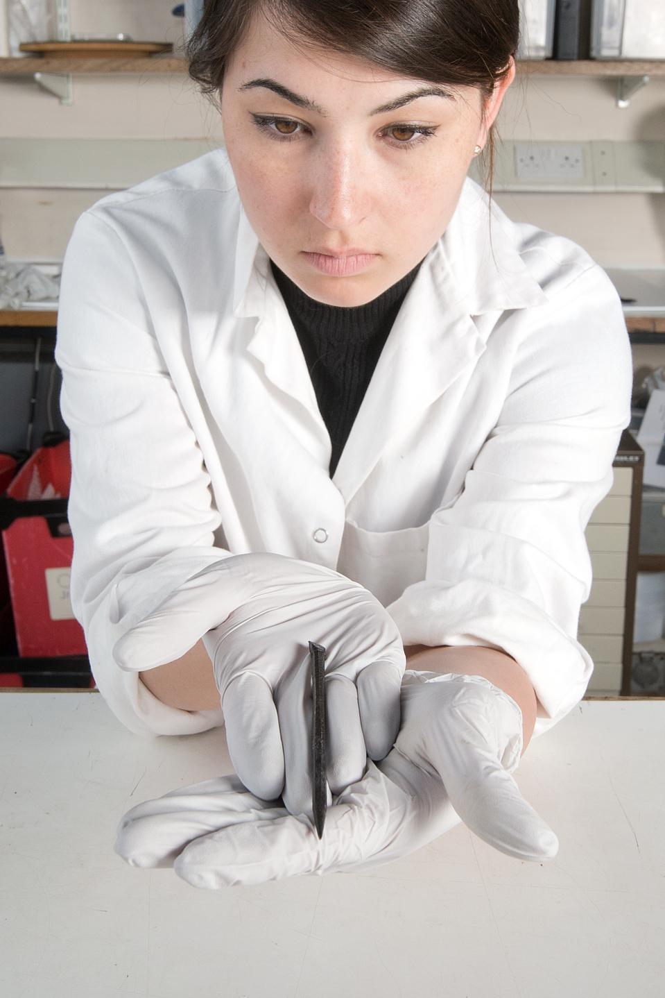 Conservator Lucie Altenburg holds Roman stylus.