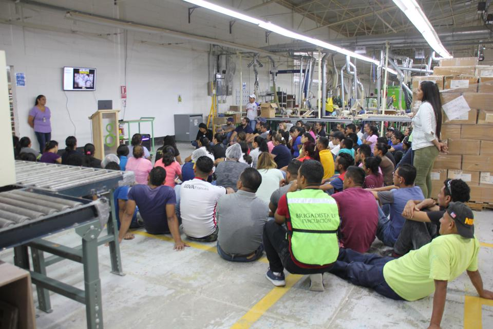 Photo of a manufacturing plant with 100 people seated on the floor participating in a meeting.