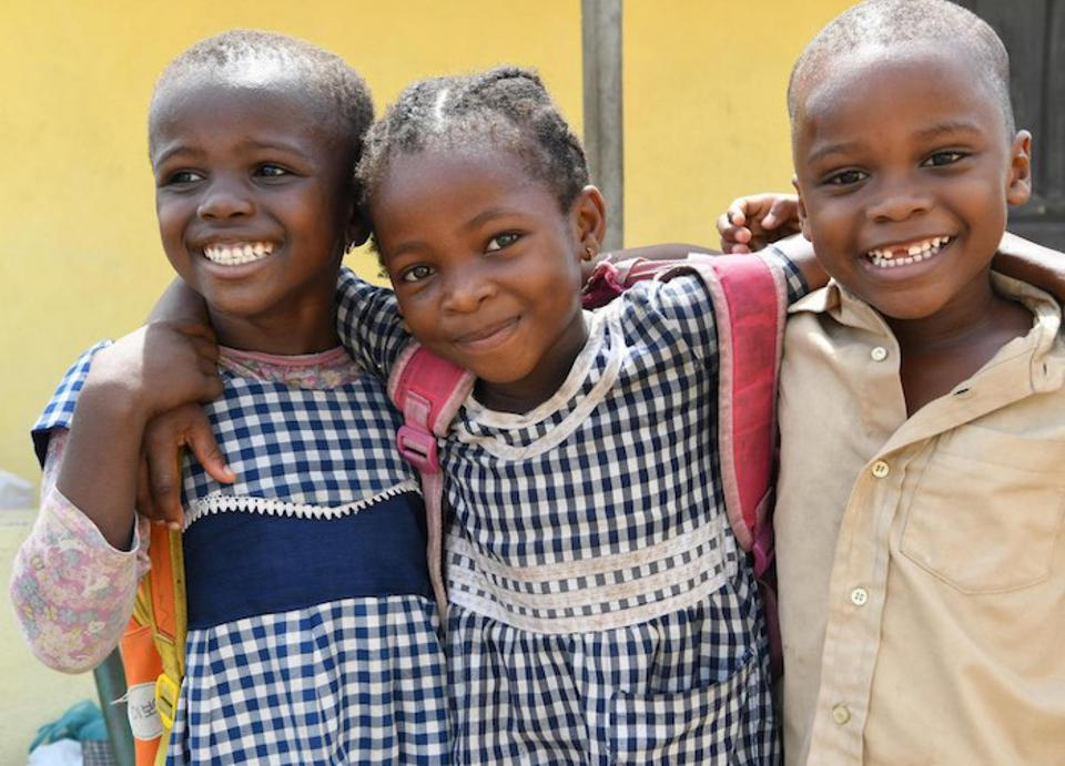 Three friends embrace outside their UNICEF-supported school in Gonzagueville, a suburb of Abidjan, the capital of Côte d'Ivoire.