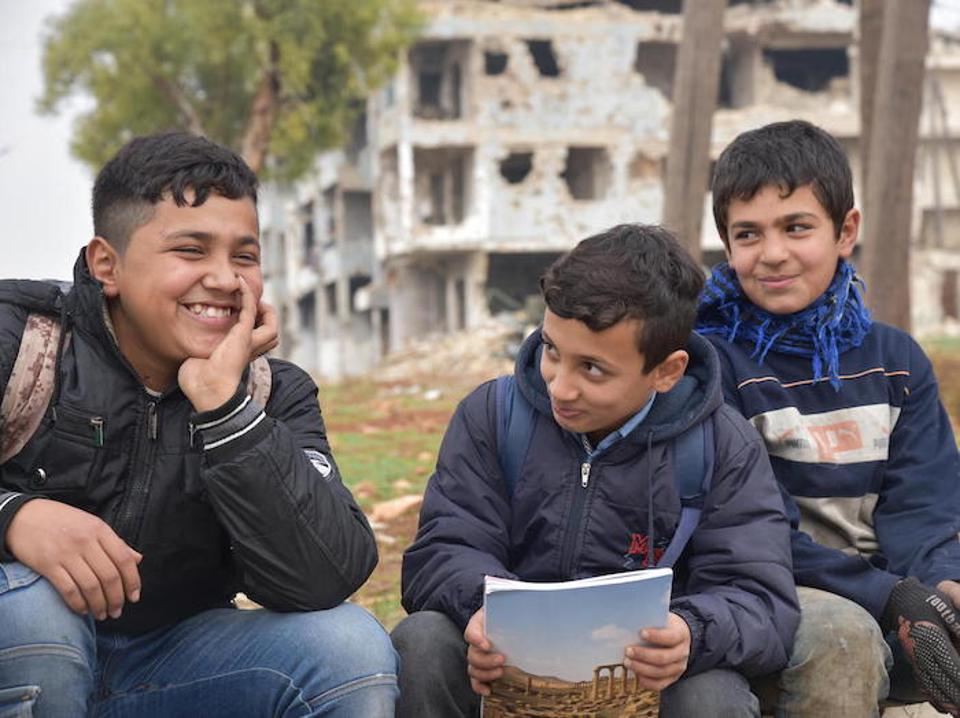 From left: Hussein and Mohamed are in school. Their friend Mustafa, 12, is not. He works to support his family.  UNICEF is working with partners to provide quality, inclusive education for all children in Syria.