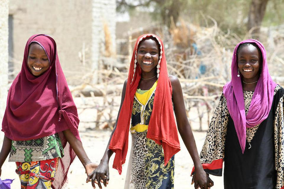 A trio of friends hold hands in the village of Bolingo, in the center of Chad. UNICEF is working with Chad's Ministry of Education and the Korean International Cooperation Agency to promote equal education opportunities for girls and boys.