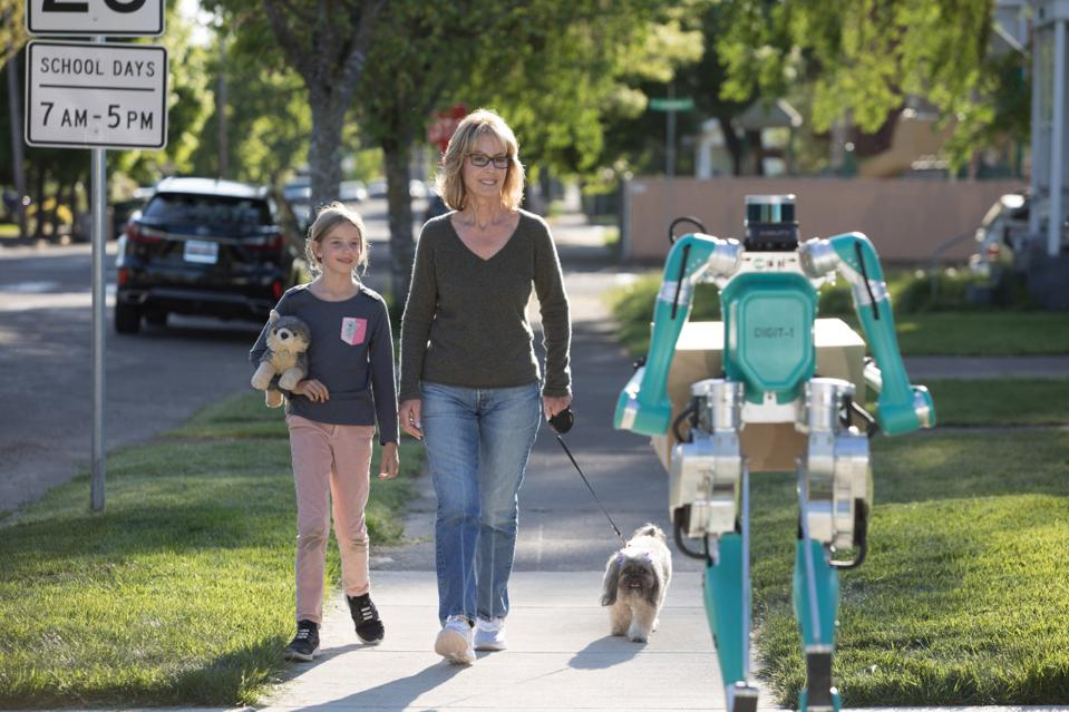A turquoise robot with a lidar puck for a head carries a package while walking down a sidewalk.