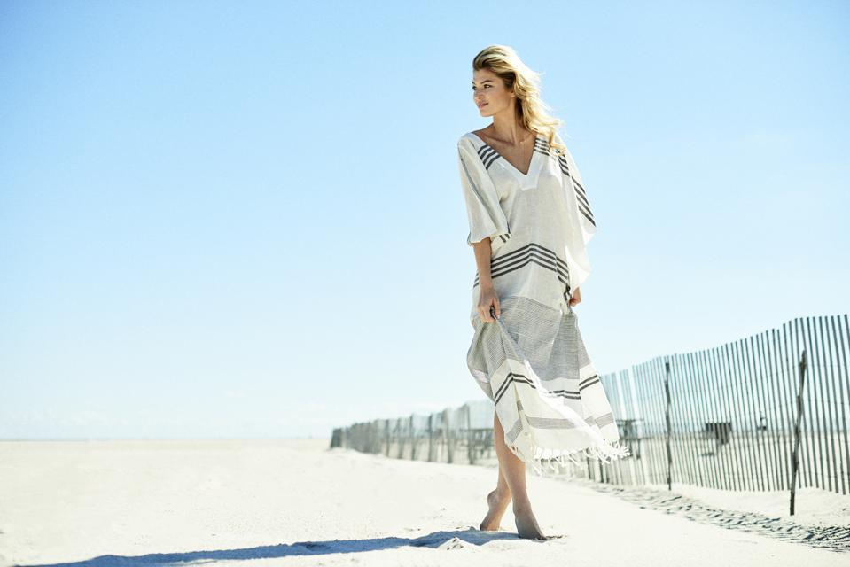 Woman wearing sustainable caftan on the beach