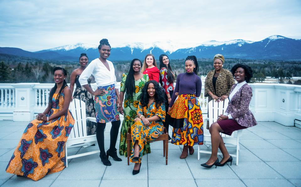A group of African women pose in front of a snow capped mountain