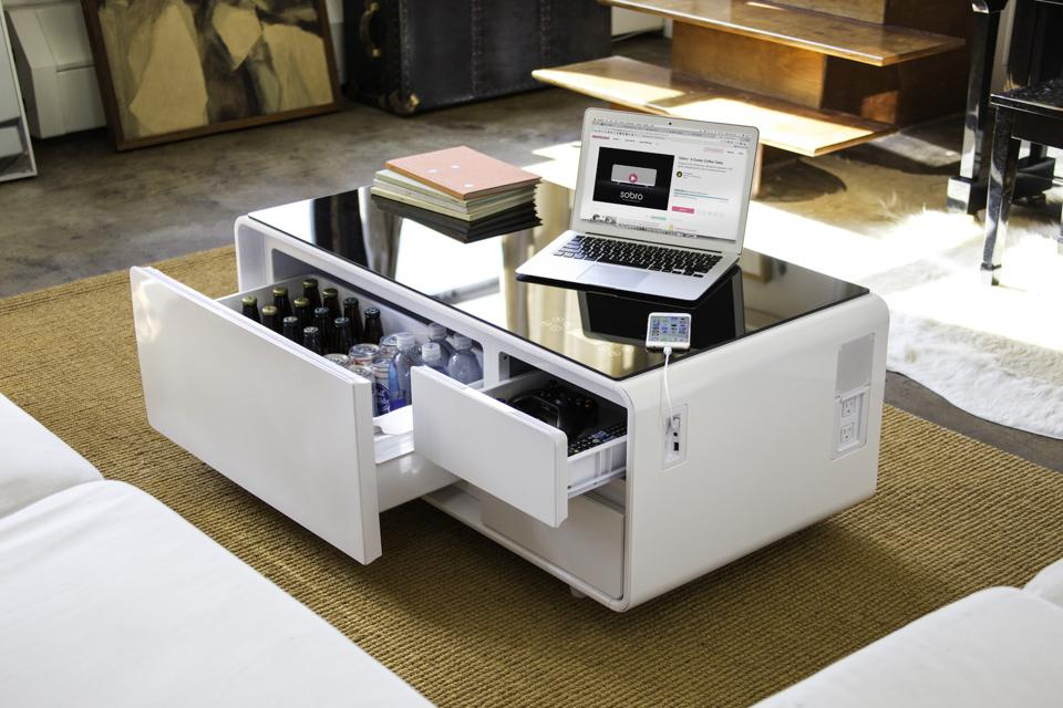 This smart coffee table includes a refrigerator drawer, bluetooth speakers, charging station, LED lights, touch control panel, tempered glass top and storage drawers.
