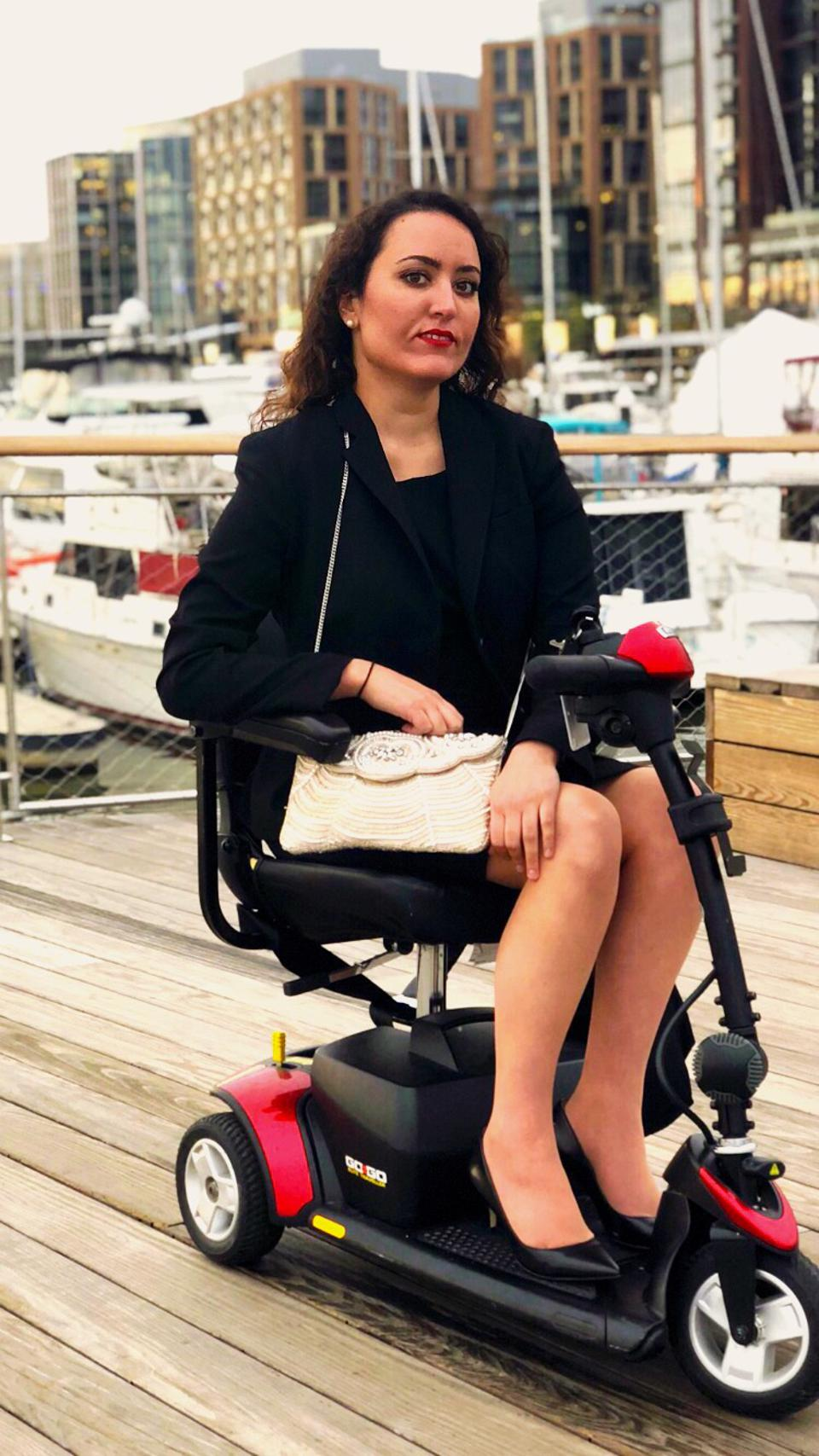 Kristin Duquette, on her motorized scooter, sits on the pier at the Washington DC Wharf.