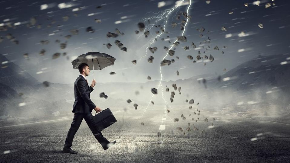 businessman walking through lightning storm