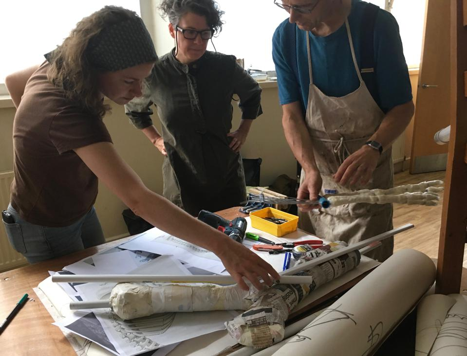 Artists creating a walrus skeleton out of repurposed materials