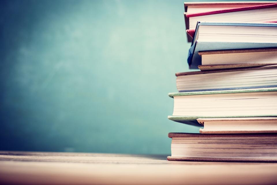 Textbooks on wooden school desk with chalkboard.