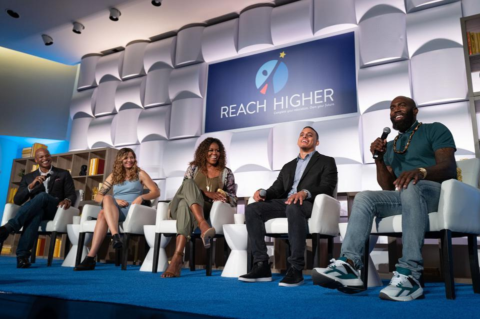 A group of panelists including Michelle Obama and Malcolm Jenkins