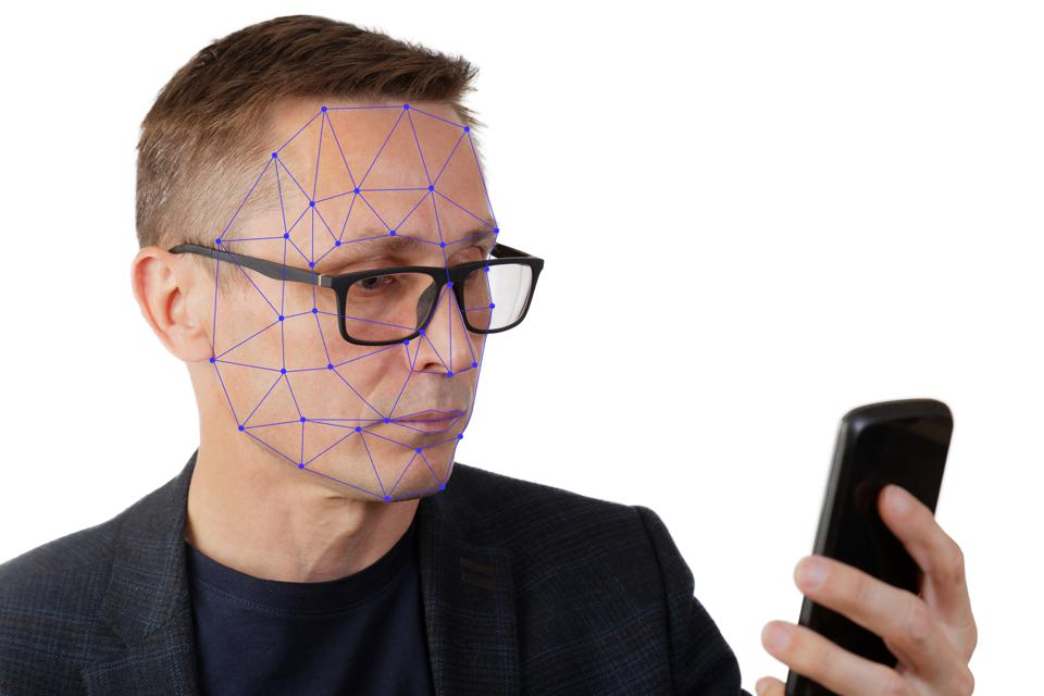 Portrait of man with smartphone using face ID recognition system.