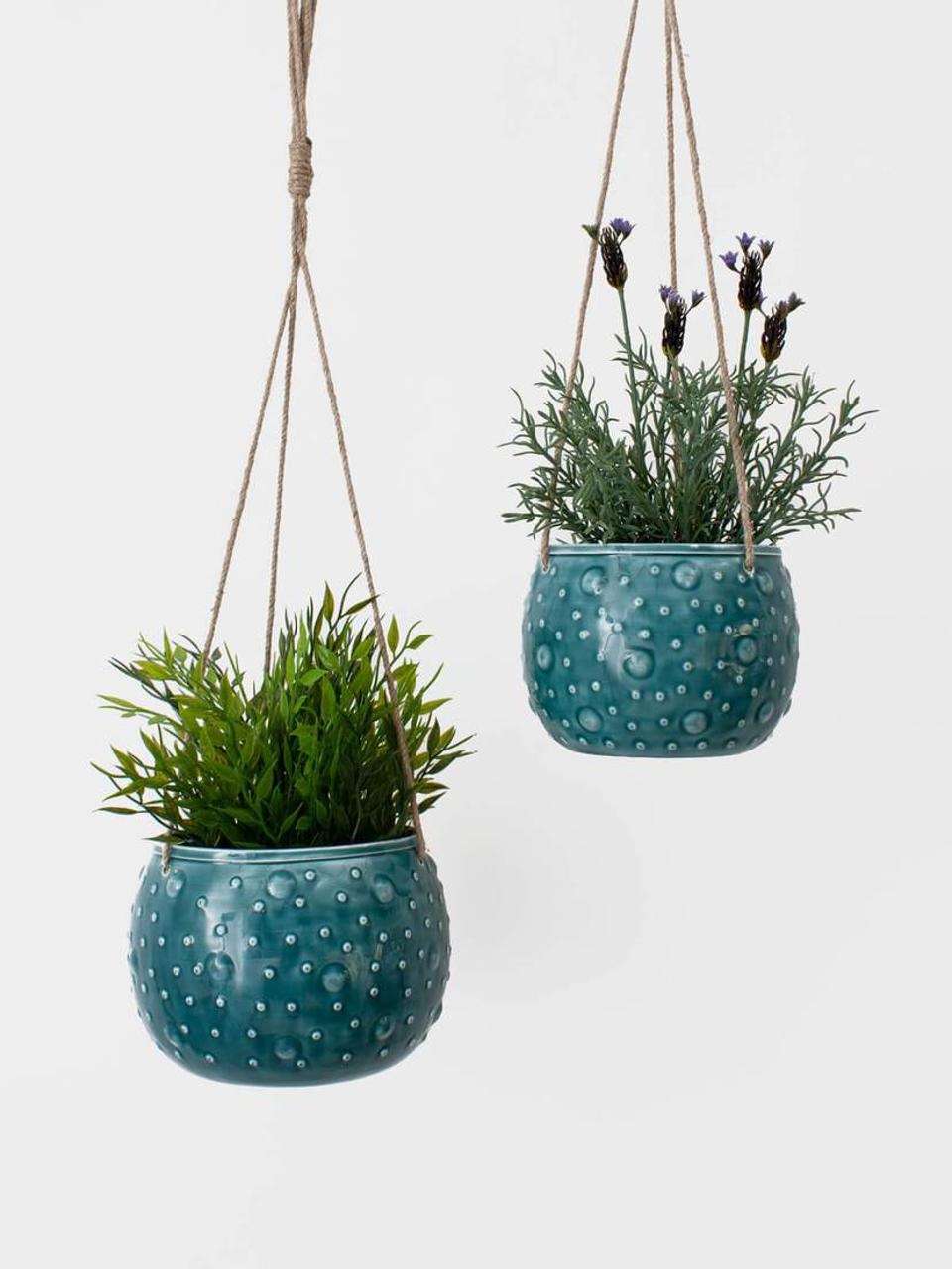 A pair of enamel hanging baskets with plants by international vendor Bohemia Design.