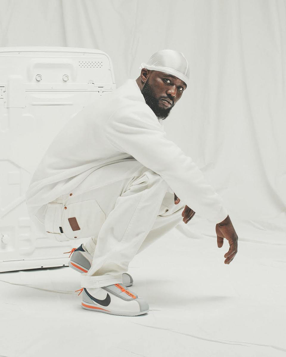 A man in all white against and all-white background wearing Nike Cortez sneakers.