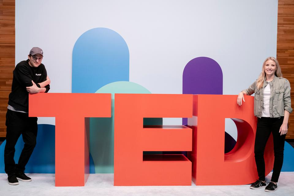Ashton Kutcher and Julie Cordua pose with the TED logo.