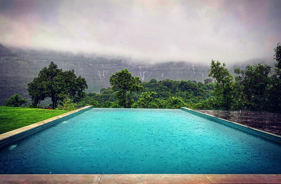 Infinity pool at the Presidential Villa of Dharana at Shillim with cascading waterfalls on the mountains.