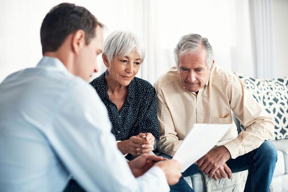 Retired couple looking over paperwork with their financial advisor