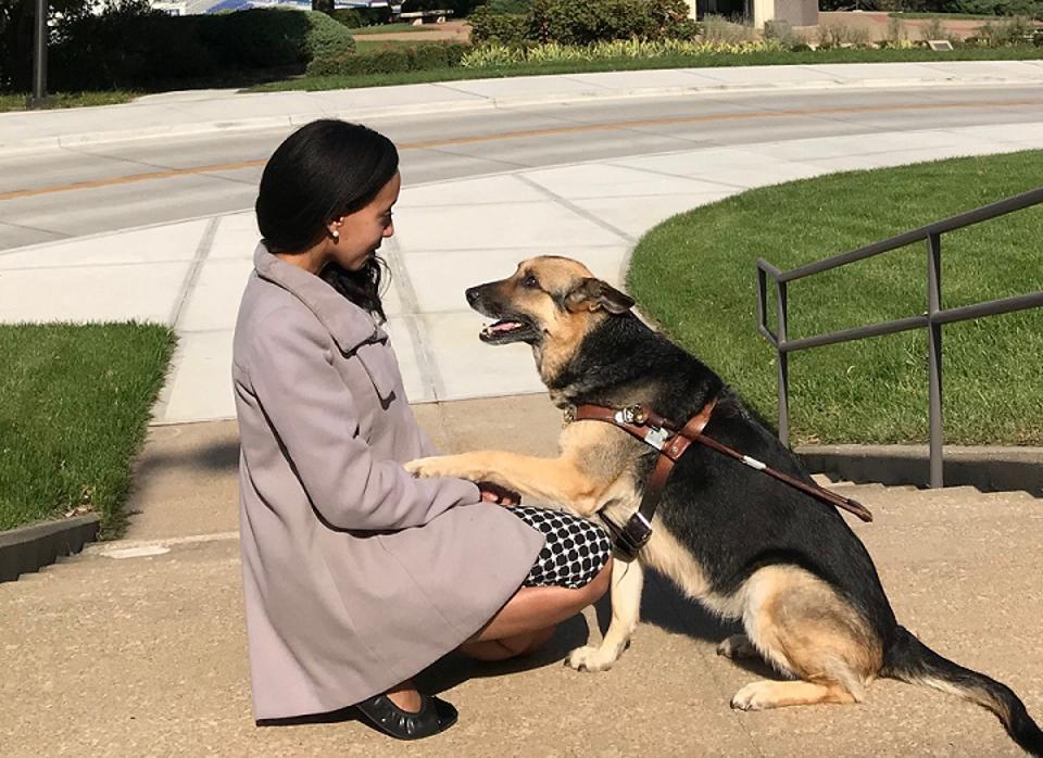 Haben Girma is kneeling by her guide dog, Maxine, who is gazing up at her.