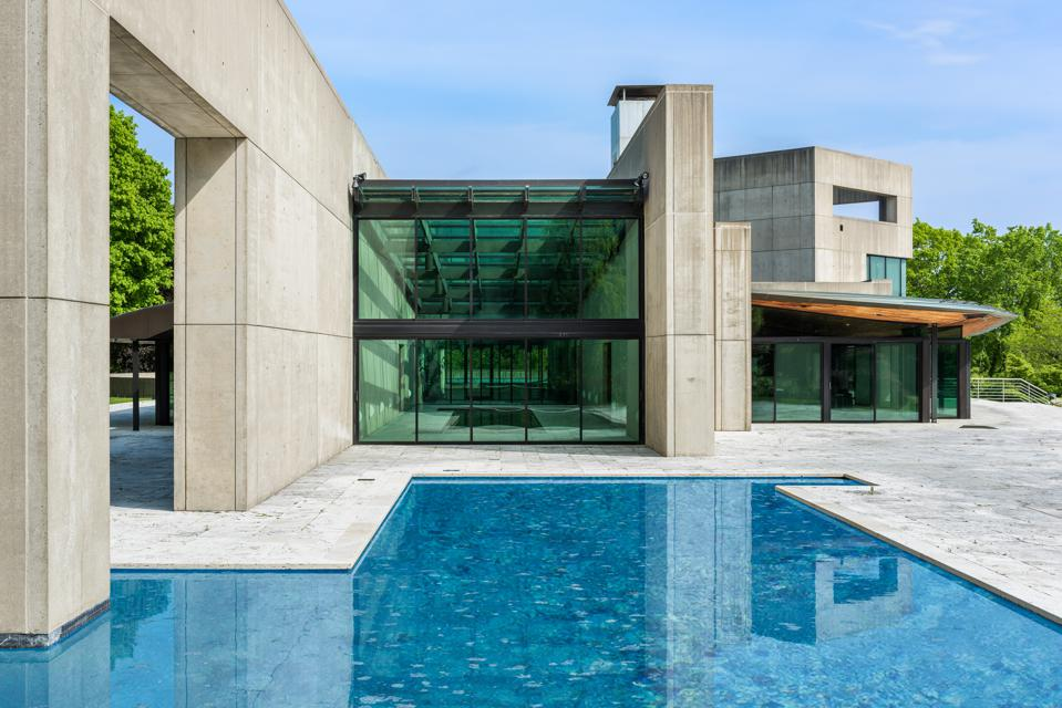 A pool in front of a concrete and glass home.