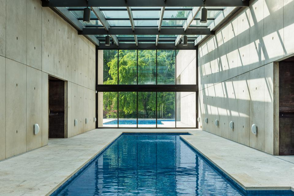 An indoor and outdoor pool separated by a wall of glass.
