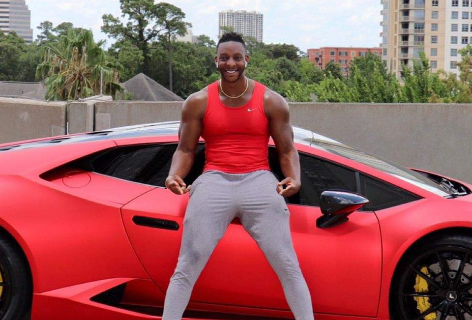 Wesley Virgin in front of red sports car.