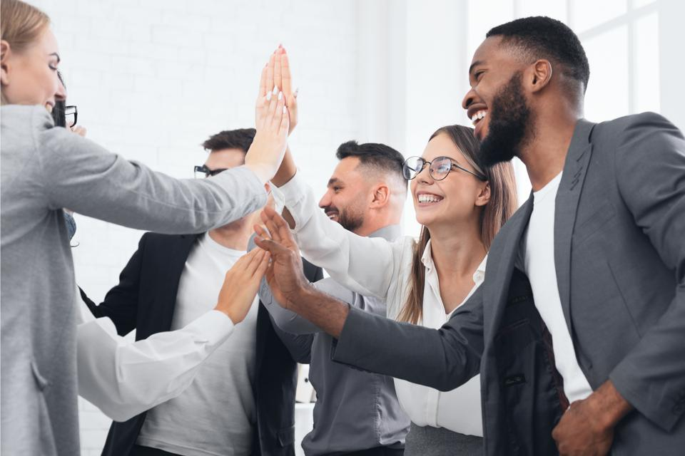 Team achievement, diverse business people giving high five