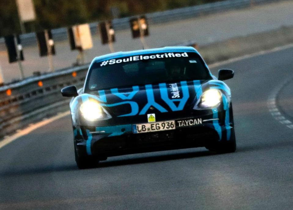 A pre-production Porsche Taycan EV lays down some miles on a test track.